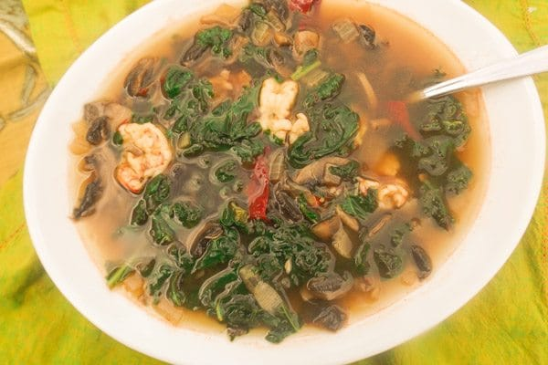 This soup called Sopa de Hongos is a delicious mushroom broth made with white mushrooms, onions, garlic, guajillo peppers, kale and shrimp.  Excellent comfort soup. | mexicanappetizersandmore.com