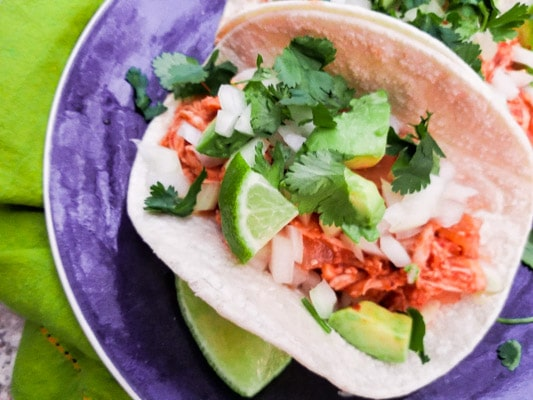 These Tacos de Tinga are made with shredded chicken, tomatoes, onions, garlic, chipotle peppers in adobo sauce, served in corn tortillas and topped with chopped onions, fresh chopped cilantro and avocado cubes.