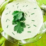 A poblano cream sauce made with roasted poblano peppers, sour cream, mayonnaise, garlic, lime juice, cilantro, salt and pepper inside a glass dipping cup and garnished with cilantro leaves and chives.