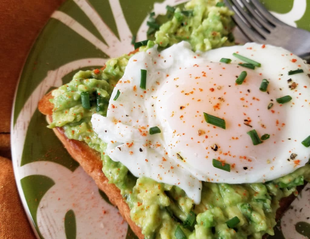 This simple poached egg and avocado toast is made with avocado spread that includes chives and cayenne pepper with a poached egg on toast. | mexicanappetizersandmore.com