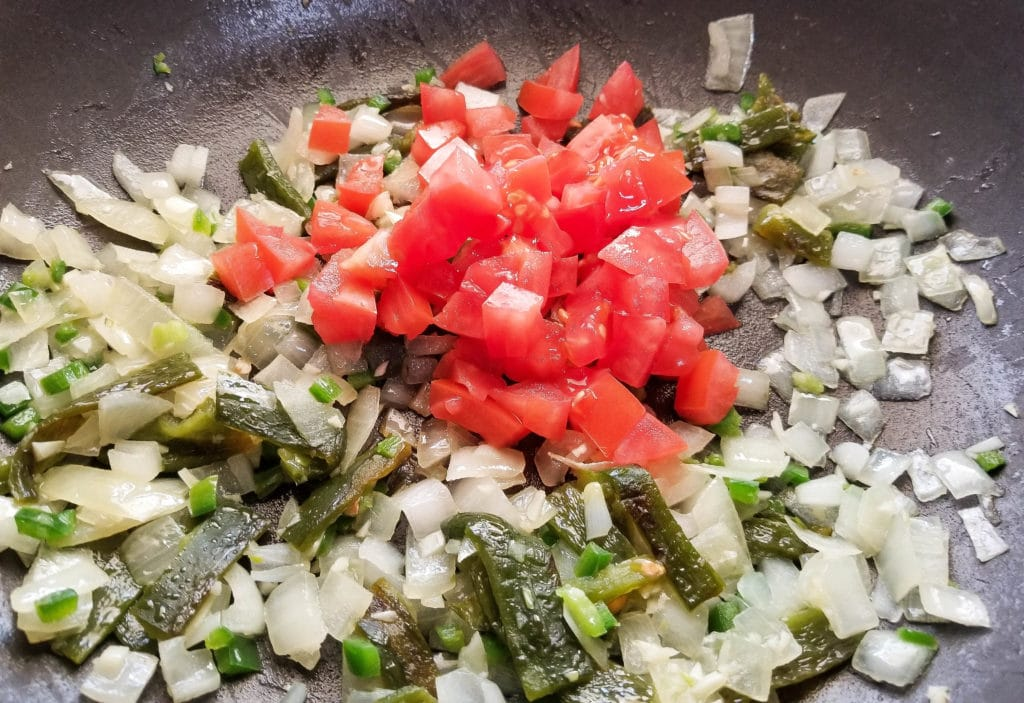 Onions, peppers, jalapeno, garlic and tomatoes cooking for authentic migas recipe. | mexicanappetizersandmore.com