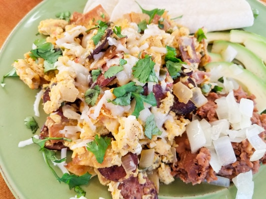 Authentic Migas Recipe with crispy corn tortilla strips, scrambled eggs with kielbasa sausage, onions, tomatoes, poblano pepper, jalapeno, garlic, cilantro, monterey jack cheese and refried beans, avocado slices on a green plate. | mexicanappetizersandmore.com