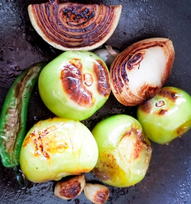 Roasting tomatillos, onion, serrano peppers, and garlic for the Best Mexican Salsa recipe.