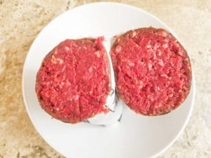 Raw ground venison meat package cut in half to show the raw ground venison meat. Fresh venison.