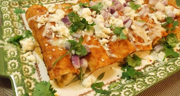 Authentic Mexican Chicken Enchiladas with Red Sauce served on a green and white platter.