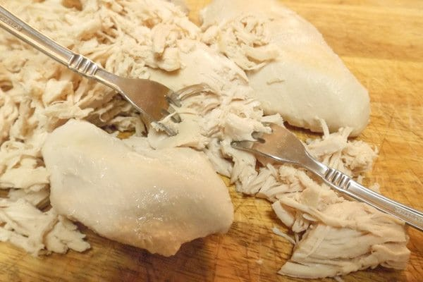 Shredding chicken breast on a wooden cutting board for the Authentic Mexican Chicken Enchiladas with Red Sauce.
