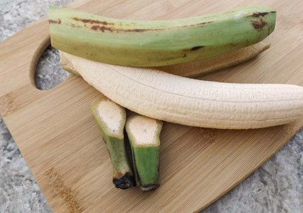 Peeled green plantain on wooden cutting board-Fried Plantains Recipe