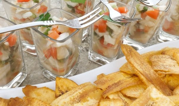 Tilapia Ceviche served in shot glasses with a side of crispy plantain chips.
