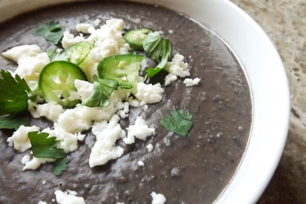 Mexican Black Bean Soup served in a white bowl and topped with cilantro, queso fresco and thinly sliced serrano peppers.