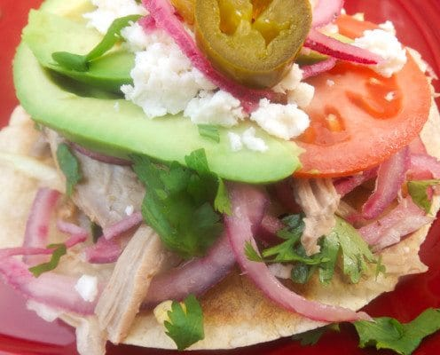 Salpicón de Cerdo (Pork Medley) This Salpicón de Cerdo (Pork Medley)-Tender pork marinated in a tasty vinaigrette, mixed with red onions, lettuce, tomatoes, cilantro, topped on crispy corn tortillas with slices of tomatoes, sliced avocado, pickled jalapeños, green chiles and queso fresco.