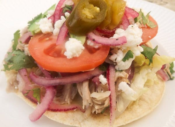 Salpicón de Cerdo (Pork Medley) This Salpicón de Cerdo (Pork Medley)-Tender pork marinated in a tasty vinaigrette, mixed with red onions, lettuce, tomatoes, cilantro, topped on crispy corn tortillas with slices of tomatoes, sliced avocado, pickled jalapeños, green chiles and queso fresco served on a white plate.