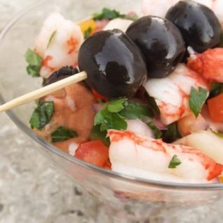 This Salpicón de Mariscos /Seafood Medley Salad recipe is made with mussels, shrimp and bay scallops., chopped yellow, red and green peppers, chopped red onions, chopped tomatoes, black olives. parsley and marinated in olive oil, red wine vinegar. lemon juice and served in martini glass.