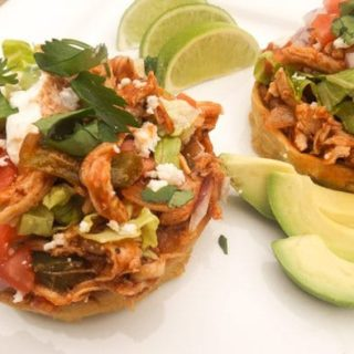 Chicken Sopes topped with all the goodies and served on a white platter with avocado slices and lime.