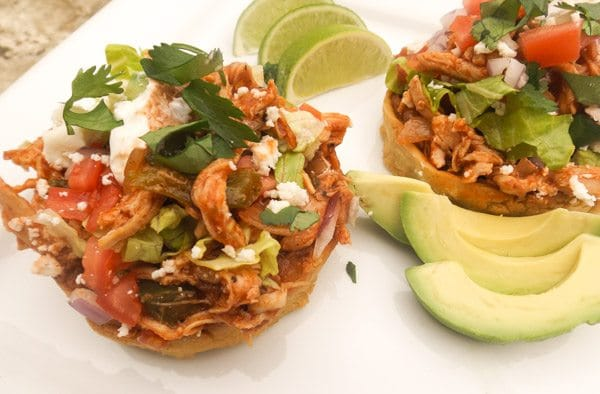 Chicken Sopes with all the toppings! Avocado, queso fresco, tomatoes, onions, salsa verde and red sauce served on a white platter.