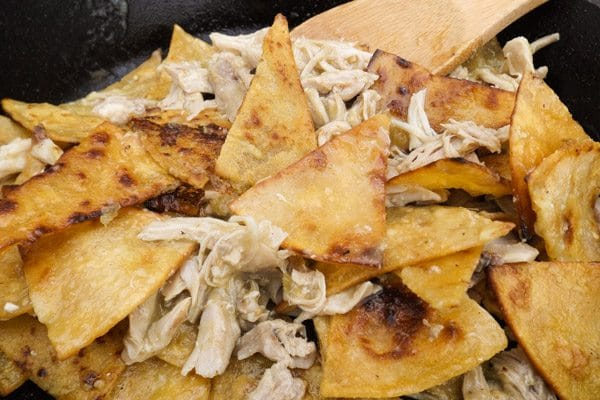 Corn tortilla chips cooked with salsa verde and shredded chicken for Chilaquiles Verdes with Chicken