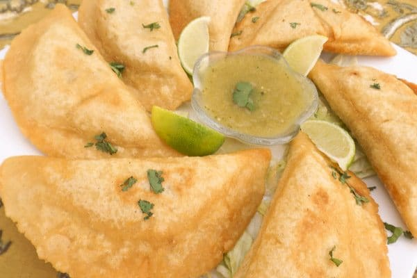 Mexican Empanadas with Green Sauce served on a white platter.