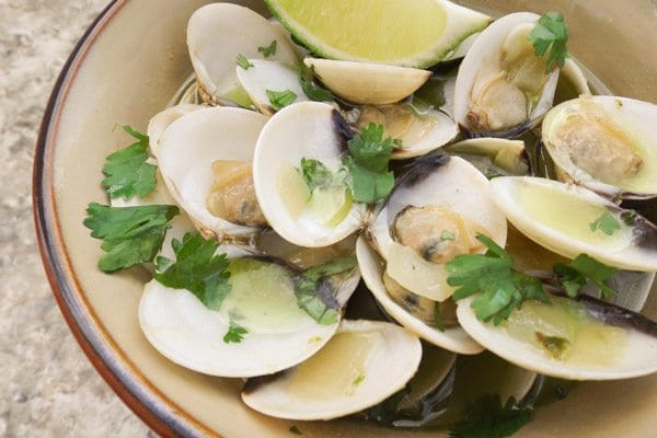 Baby Clams in Serrano Sauce served in a brown bowl and topped with fresh parsley.