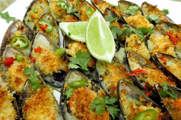 Baked Mussels made with white wine, garlic, fresh bread crumbs and topped with a sliver of serrano pepper with limes.
