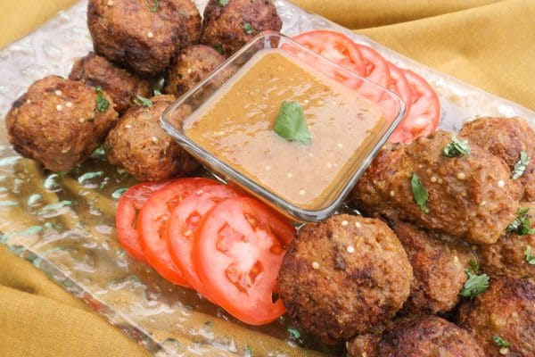 Best Turkey Meatballs with Serrano Chipotle Sauce served on a tranparent platter with sliced roma tomatoes and serrano dipping sauce.