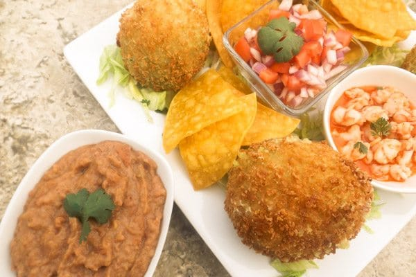 Fried Avocado Stuffed with Shrimp refried beans, pico de gallo and tortilla chips on top of a white platter.