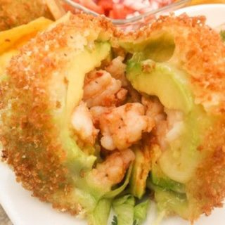 Fried Avocado Stuffed with Shrimp served on a white platter.