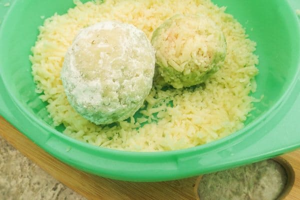 Covering avocado balls with cheese to make Fried Avocado Stuffed with Shrimp in a green bowl.