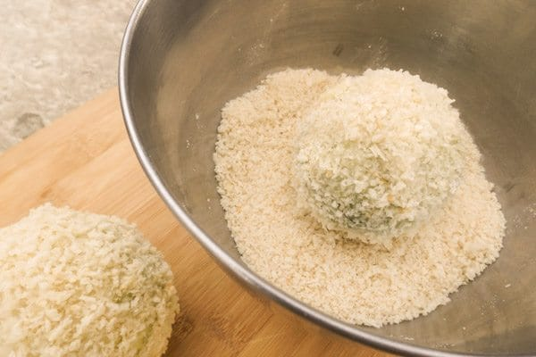 Covering avocado ball with panko crumbs for Fried Avocado Stuffed with Shrimp in bowl.