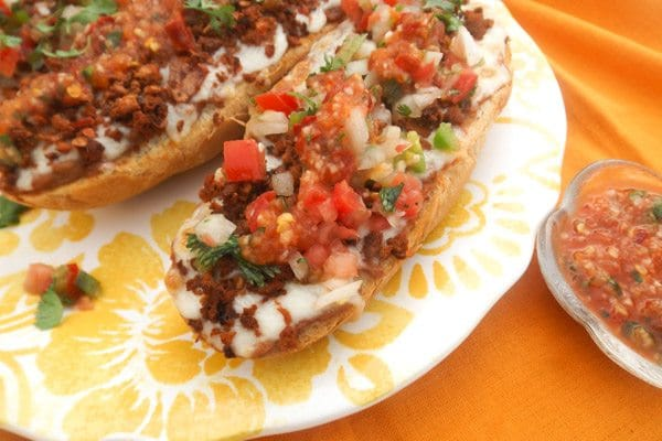 Molletes Mexicanos (Mexican Molletes)-Crusty french baguettes topped with refried beans, mozzerella cheese, savory turkey chorizo, pico de gallo and a delicious tomato arbol pepper sauce served on a yellow platter.