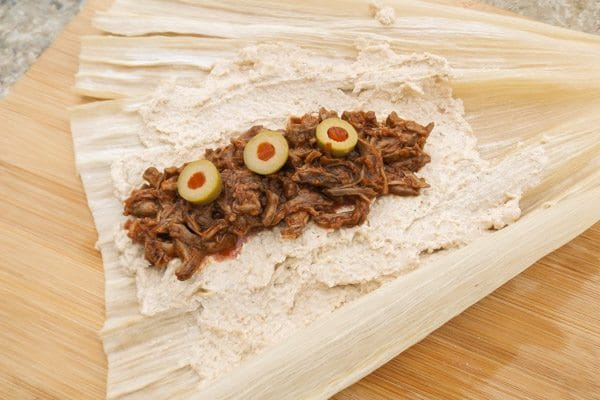 Savory beef added to masa dough on corn husk with olives on top of beef-Beef Mexican Tamales