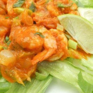 Camarones al Chipotle (Chipotle Shrimp or Spicy Chipotle Shrimp) served on a bed of lettuce with lime wedges.