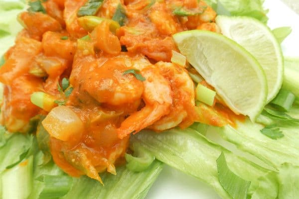 Camarones al Chipotle (Chipotle Shrimp) are made with white onions, scallions, garlic, white wine, cilantro in a tomato chipotle hot sauce and served on a bed of lettuce and limes.
