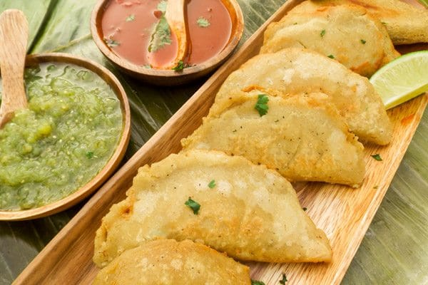 These Beef Empanadas are so tasty, hyper yummy and very simple to make.   Made with a corn masa dough and a savory beef filling. Served on a wooden platter on top of a plantain leaf with salsa verde and red guajillo pepper sauce.