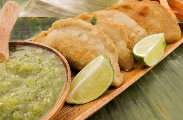Beef Empanadas served with salsa verde on a wooden platter.