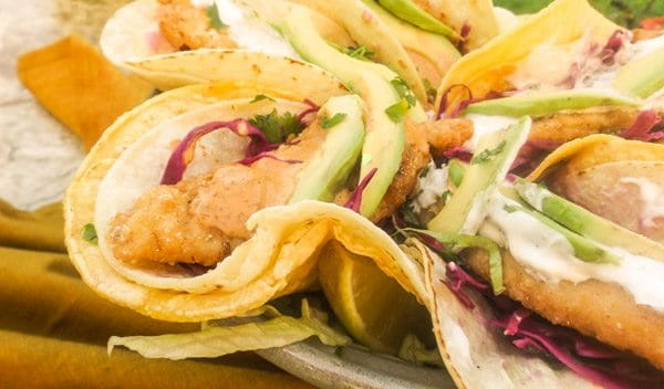 Tilapia Fish Tacos topped with a red cabbage slaw with red onions and cilantro, topped with a creamy fish sauce and avocado slices.