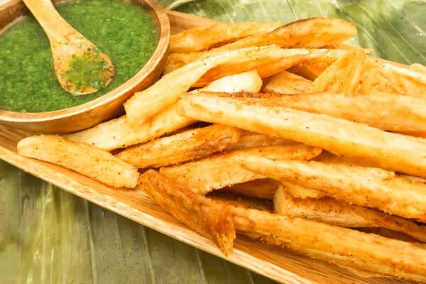 Yuca Fries with Cilantro Aioli served on a wooden platter on top of plantain leaves.