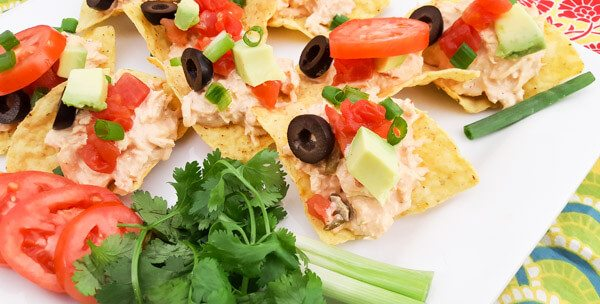 Chicken Tinga Tostaditas-shredded chicken with chipotle mayo, onions, tomatoes, scallions, cilantro, black olives, avocado on top of tortilla chips and served on a white platter.