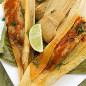 Mexican Tamales served on top of plantain leaves on a white plate.
