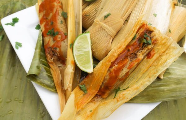 Beef Mexican Tamales served on top of plantain leaves on a white platter.