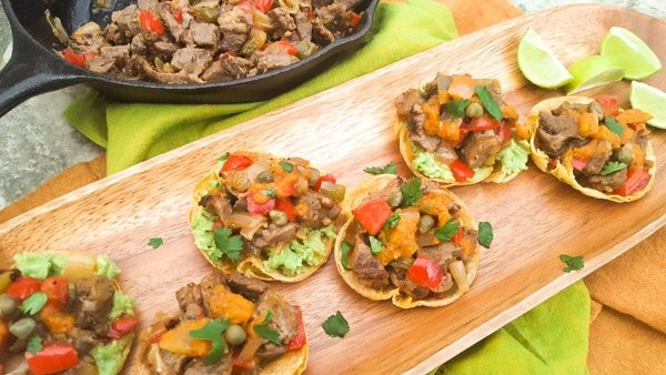 Steak Tortilla Cups served on top of a wooden platter with a cast iron skillet filled with more steak mixture beside it.