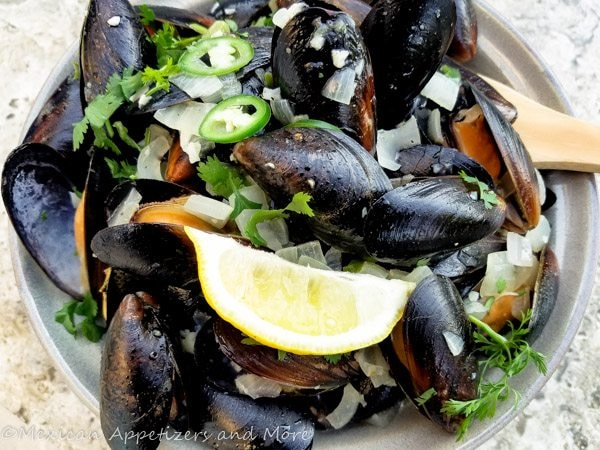 Spicy Mussels in White Wine Sauce served in light green bowl.