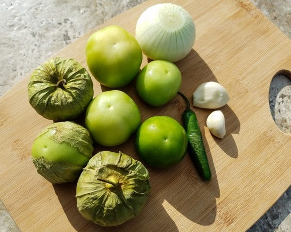 Ingredients for tomatillo serrano sauce on a wooden cutting board for the Mini Serrano Chicken Kabobs