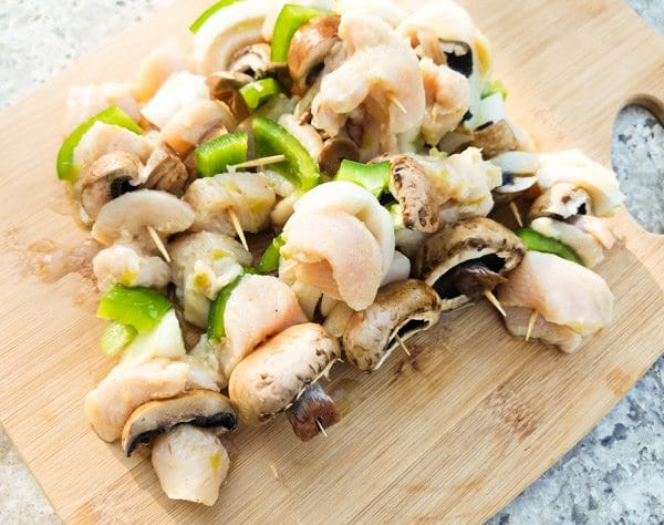 Threaded chicken kabobs on a wooden cutting board-Mini Serrano Chicken Kabobs