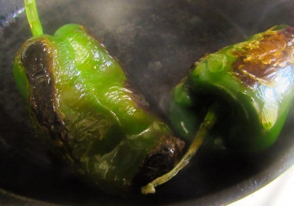 Roasted poblano peppers in cast iron skillet for Tacos Rajas Poblanas