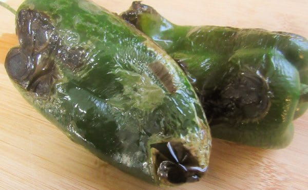 Roasted poblano peppers on wooden cutting board for Tacos Rajas Poblanas