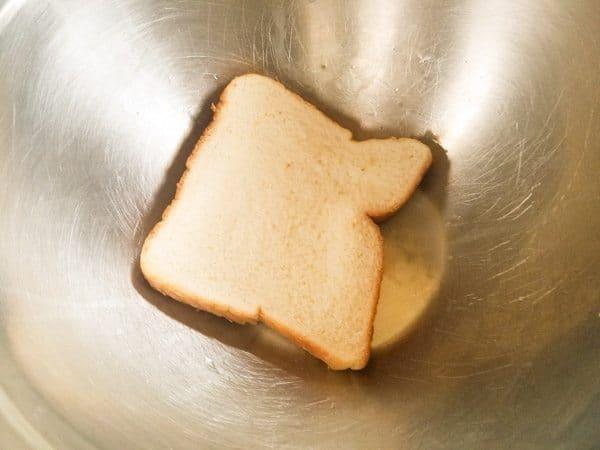 Slice of sandwich bread in bowl for fresh breadcrumbs for Albondigas en Salsa de Chipotle-Meatballs in Chipotle Sauce.