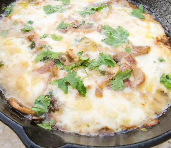 Garlic and Mushroom Queso Fundido Dip baked in a cast iron skillet.
