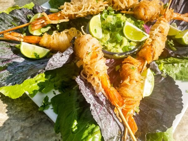 Pinchos de Camarones served on a bed of cabbage with avocado jalapeno dip.