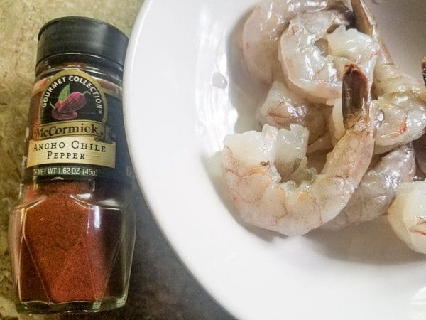 Raw Shrimp in a white bowl and ancho chili pepper seasoning jar- Pinchos de Camarones