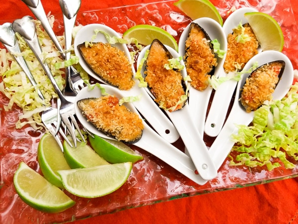 These Easy Mexican Asian Baked Mussels are made with Gourmet Japanese sauce, onions, jalapeños, tomatoes, garlic and panko bread crumbs.  Creamy, tender and delicious with a crispy panko topping. Individual mussels served on Asian soup spoons on top of a clear platter with shredded lettuce and limes.