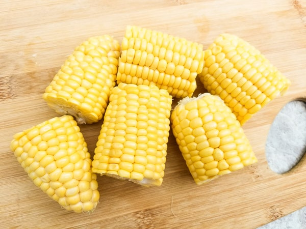 Ear corns cut on wooden cutting boards-Easy Delicious Mexican Street Corn (Elote)